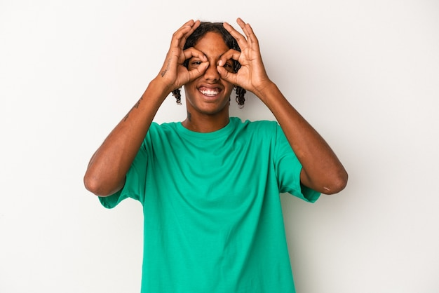Young african american man isolated on white background showing okay sign over eyes