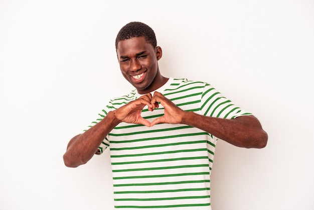 Young african american man isolated on white background smiling and showing a heart shape with hands.