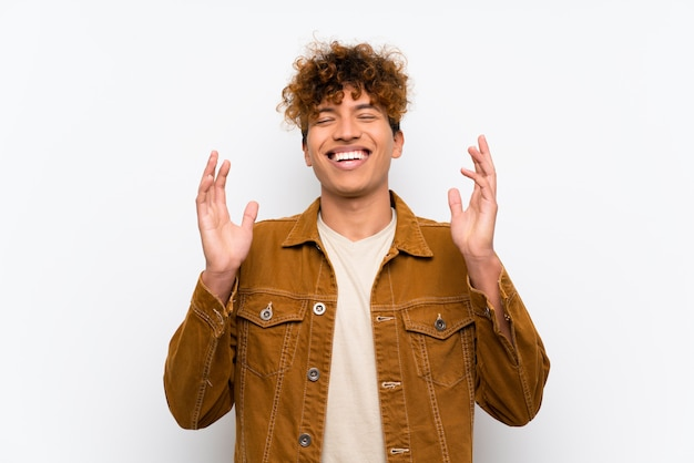 Young african american man over isolated white wall laughing