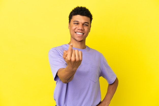 Young african american man isolated on yellow background doing coming gesture