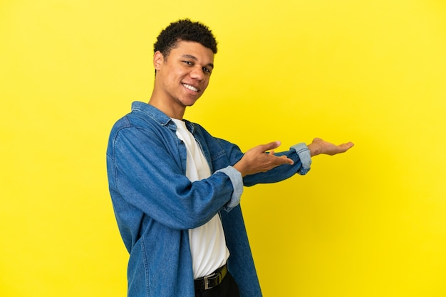 Young african american man isolated on yellow background extending hands to the side for inviting to come