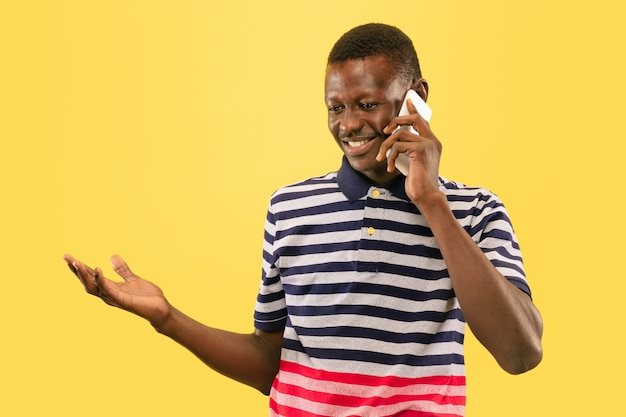 Young african-american man isolated on yellow studio background, human emotions concept