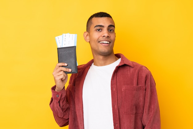 Young african american man over isolated yellow wall happy in vacation with passport and plane tickets