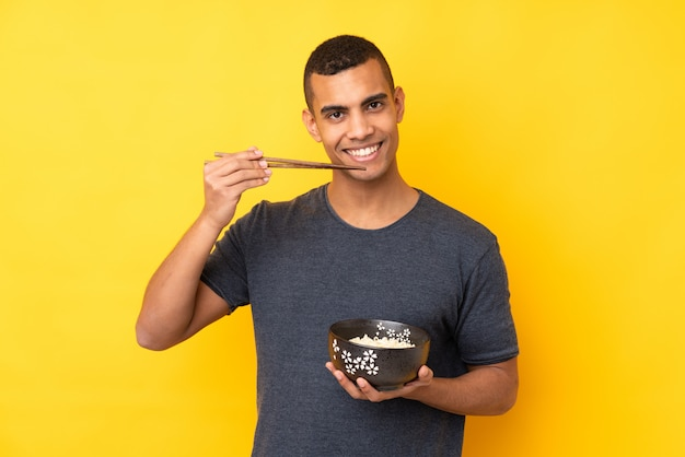 Young african american man over isolated yellow wall holding a bowl of noodles with chopsticks