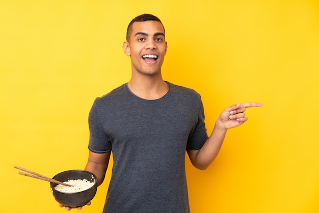 Young african american man over isolated yellow wall surprised and pointing finger to the side while holding a bowl of noodles with chopsticks