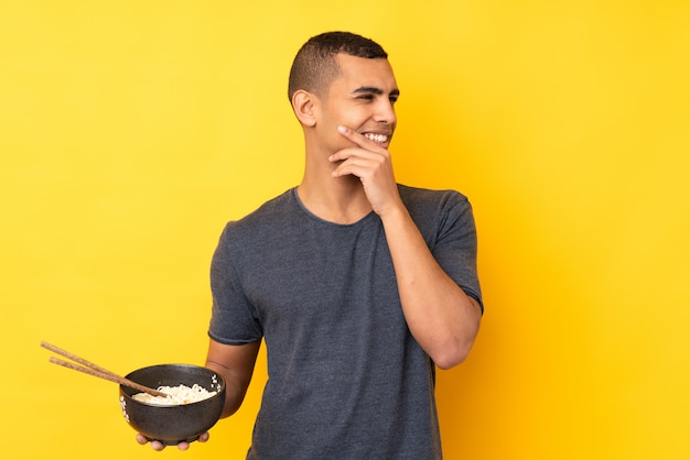 Young african american man over isolated yellow wall thinking an idea and looking side while holding a bowl of noodles with chopsticks
