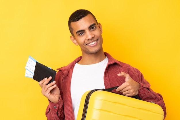 Young african american man over isolated yellow wall in vacation with suitcase and passport