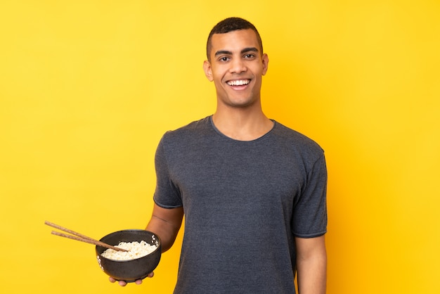 Young african american man over isolated yellow wall with surprise and shocked facial expression while holding a bowl of noodles with chopsticks