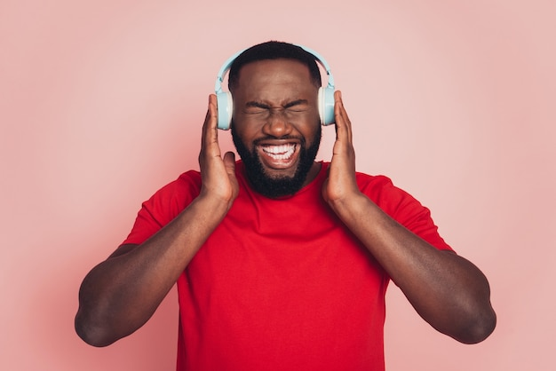 Young african american man listen loud music headset over pink background