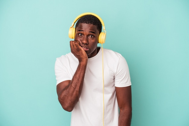 Young african american man listening to music isolated on blue background biting fingernails, nervous and very anxious.