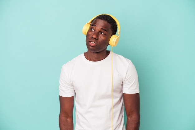 Young african american man listening to music isolated on blue background dreaming of achieving goals and purposes