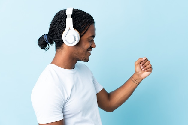 Young african american man listening music isolated