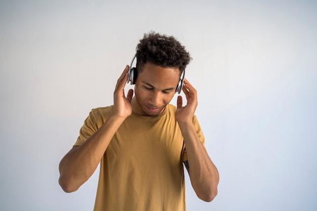 무선 헤드폰을 사용하여 펑키 음악을 듣고 젊은 아프리카 계 미국인 남자.
