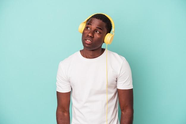 目標と目的を達成することを夢見て青い背景で隔離の音楽を聞いている若いアフリカ系アメリカ人の男