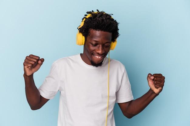 青い背景で隔離の音楽を聞いている若いアフリカ系アメリカ人の男は、秘密のホットブレーキのニュースを言って脇を見ています