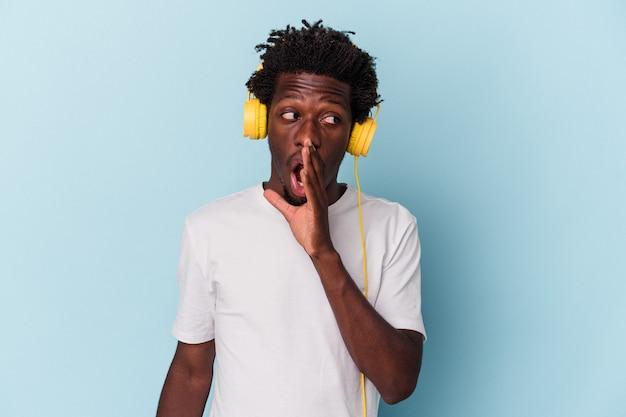 青い背景で隔離の音楽を聞いている若いアフリカ系アメリカ人の男は、秘密の熱いブレーキングニュースを言って脇を見ています