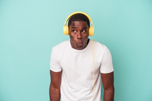 青い背景に分離された音楽を聞いている若いアフリカ系アメリカ人の男は、肩をすくめると混乱した目を開いています。