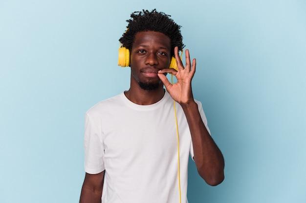 秘密を保持している唇に指で青い背景に分離された音楽を聞いている若いアフリカ系アメリカ人の男。