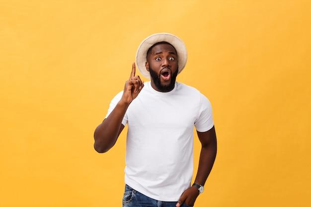 Молодой афроамериканец смотрит вверх с задумчивым и скептическим выражением лица, держа палец на подбородке, пытаясь что-то вспомнить.