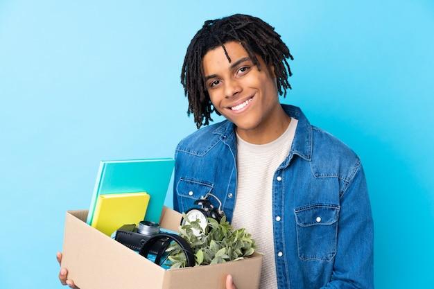 Молодой афроамериканец человек делает ход, поднимая коробку с вещами