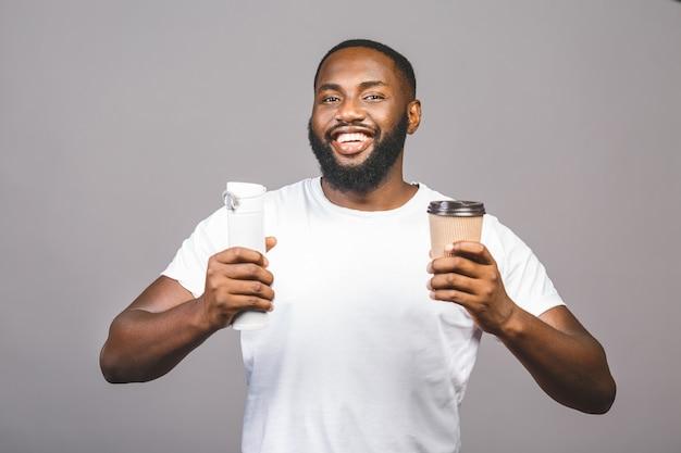 Молодой делать человека афроамериканца выбирает между чашкой кофе и рециркулирует одно положение над изолированной серой предпосылкой.
