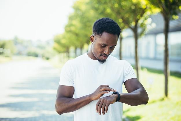 若いアフリカ系アメリカ人の男性は、公園で白いtシャツを着て朝のジョギングをし、フィットネスのアクティブなライフスタイルに従事するスマートウォッチフィットネスブレスレットのスポーツプログラムを切り替えます