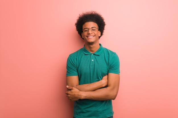 Молодой афроамериканец на розовой стене скрещивает руки, улыбается и расслабляется