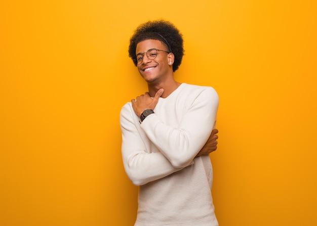 포옹을주는 오렌지 벽에 젊은 아프리카 계 미국인 남자