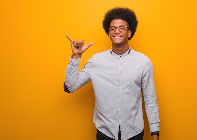 Young african american man over an orange wall doing a rock gesture