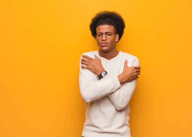 Young african american man over an orange wall going cold due to low temperature