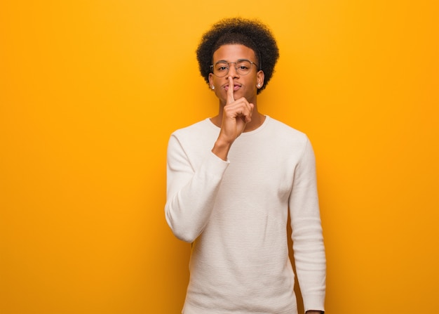 Young african american man over an orange wall keeping a secret