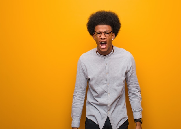 Young african american man over an orange wall screaming very angry and aggressive