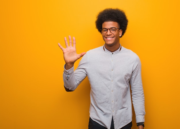 Young african american man over an orange wall showing number five