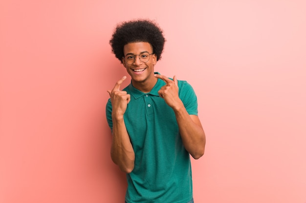 ピンクの壁の上の若いアフリカ系アメリカ人の男は、口を指して微笑む