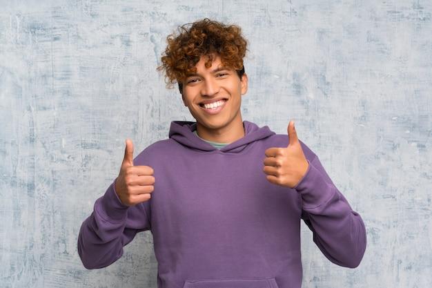 Молодой афроамериканец человек над стеной гранж, давая пальцы вверх жест