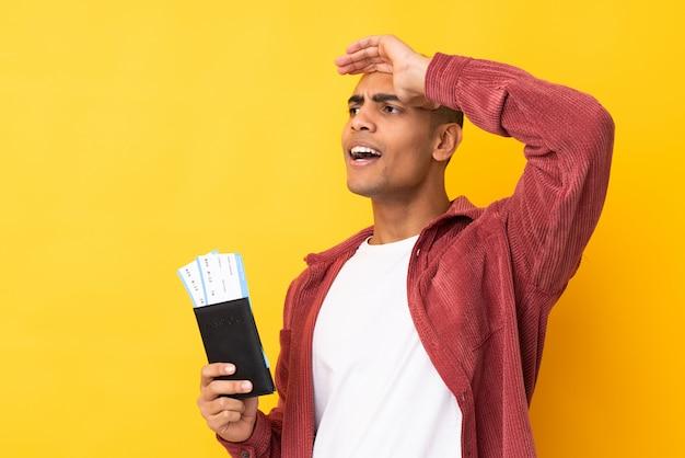 遠くに何かを見ながらパスポートと飛行機のチケットと休暇で孤立した黄色の壁の上の若いアフリカ系アメリカ人の男