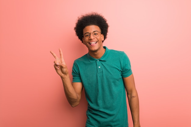 Young african american man over a pink wall doing a gesture of victory