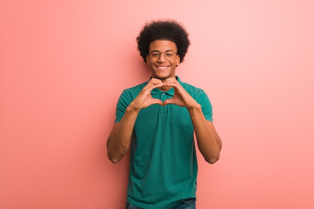 Young african american man on a pink wall doing a heart shape with hands