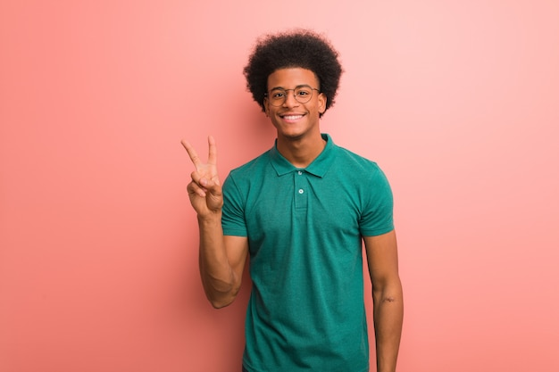 Young african american man over a pink wall fun and happy doing a gesture victory