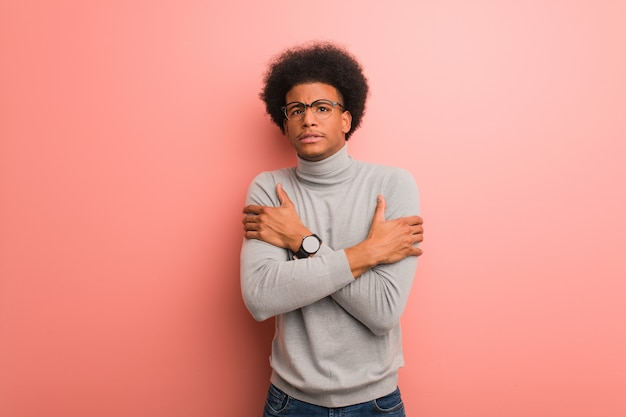 Young african american man over a pink wall going cold due to low temperature