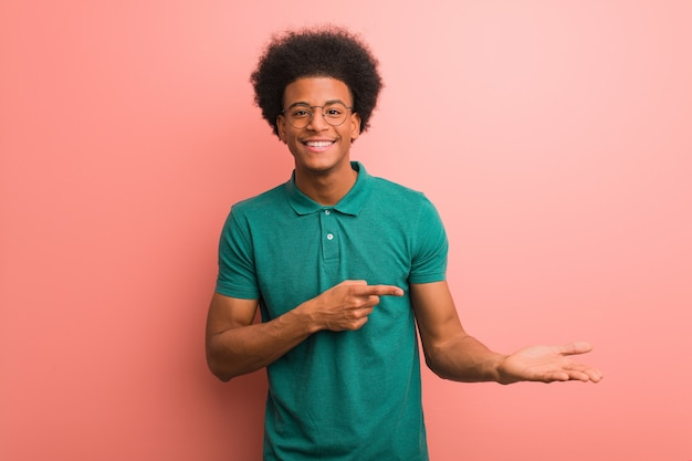Young african american man over a pink wall holding something with hand
