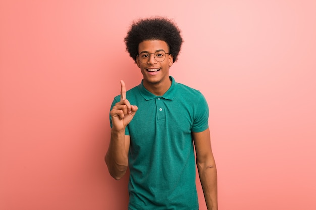 Young african american man over a pink wall showing number one
