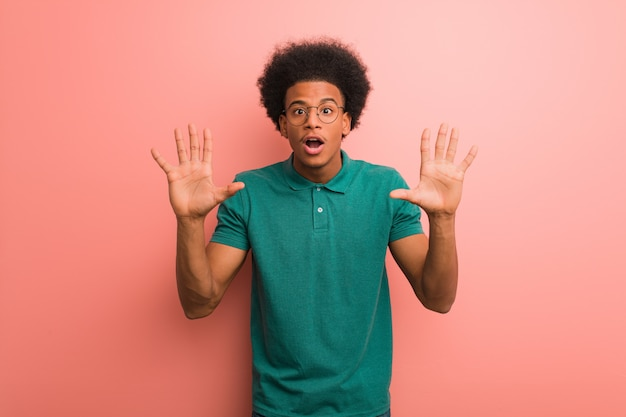 Young african american man over a pink wall showing number ten