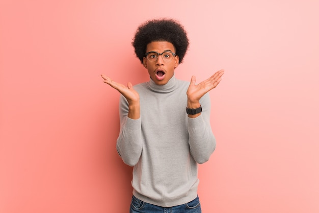 Young african american man over a pink wall surprised and shocked