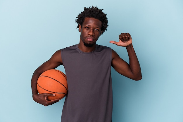 Young african american man playing basketball isolated on blue background feels proud and self confident, example to follow.