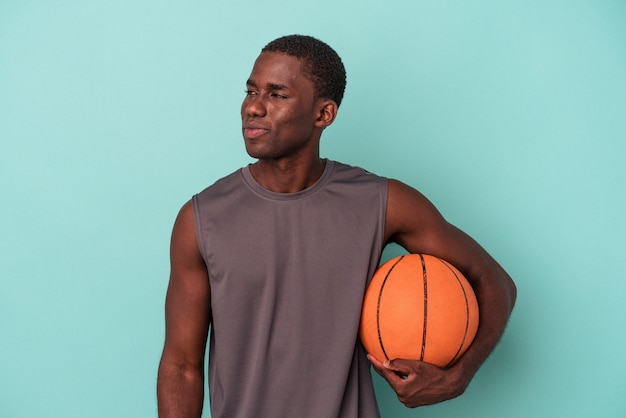 Young african american man playing basketball isolated on blue background looks aside smiling, cheerful and pleasant.