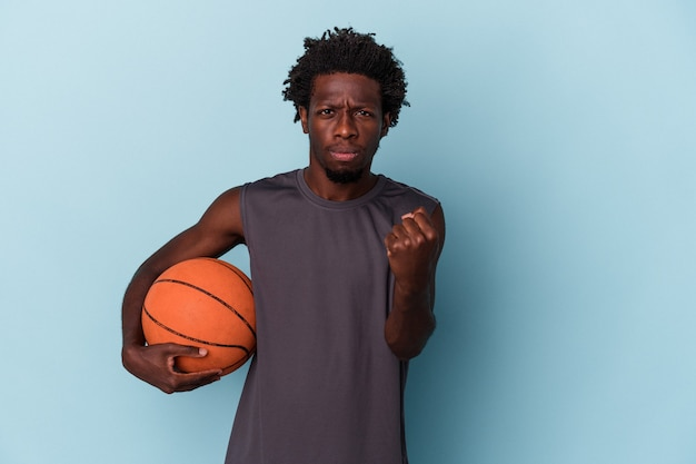 Young african american man playing basketball isolated on blue background showing fist to camera, aggressive facial expression.