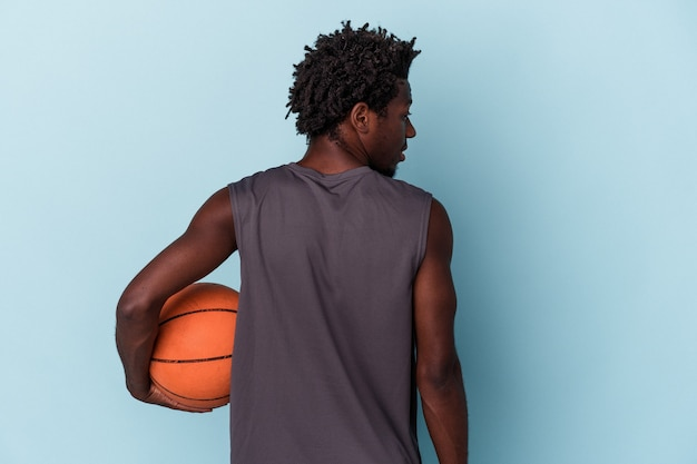 Young african american man playing basketball isolated on blue background