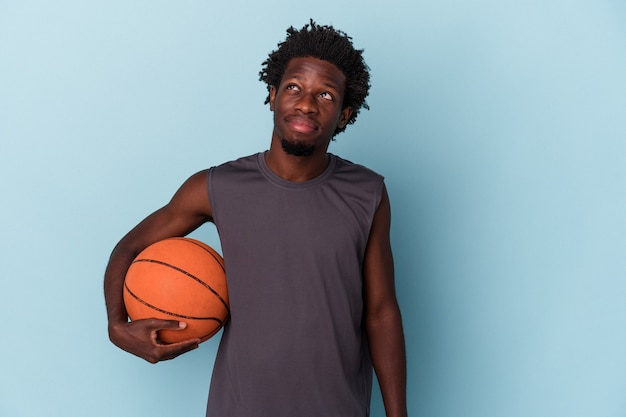 目標と目的を達成することを夢見て青い背景で隔離のバスケットボールをしている若いアフリカ系アメリカ人の男