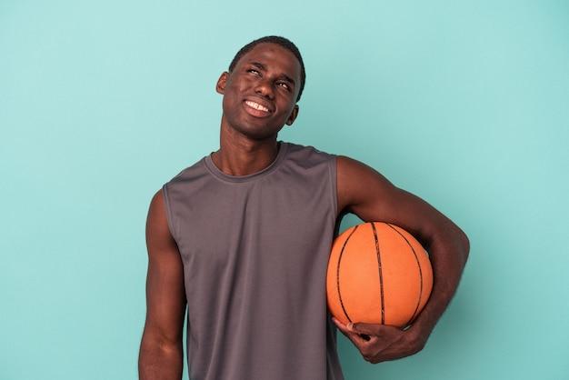 목표와 목적을 달성하는 꿈을 꾸고 파란색 배경에 고립 농구를 하는 젊은 아프리카계 미국인 남자